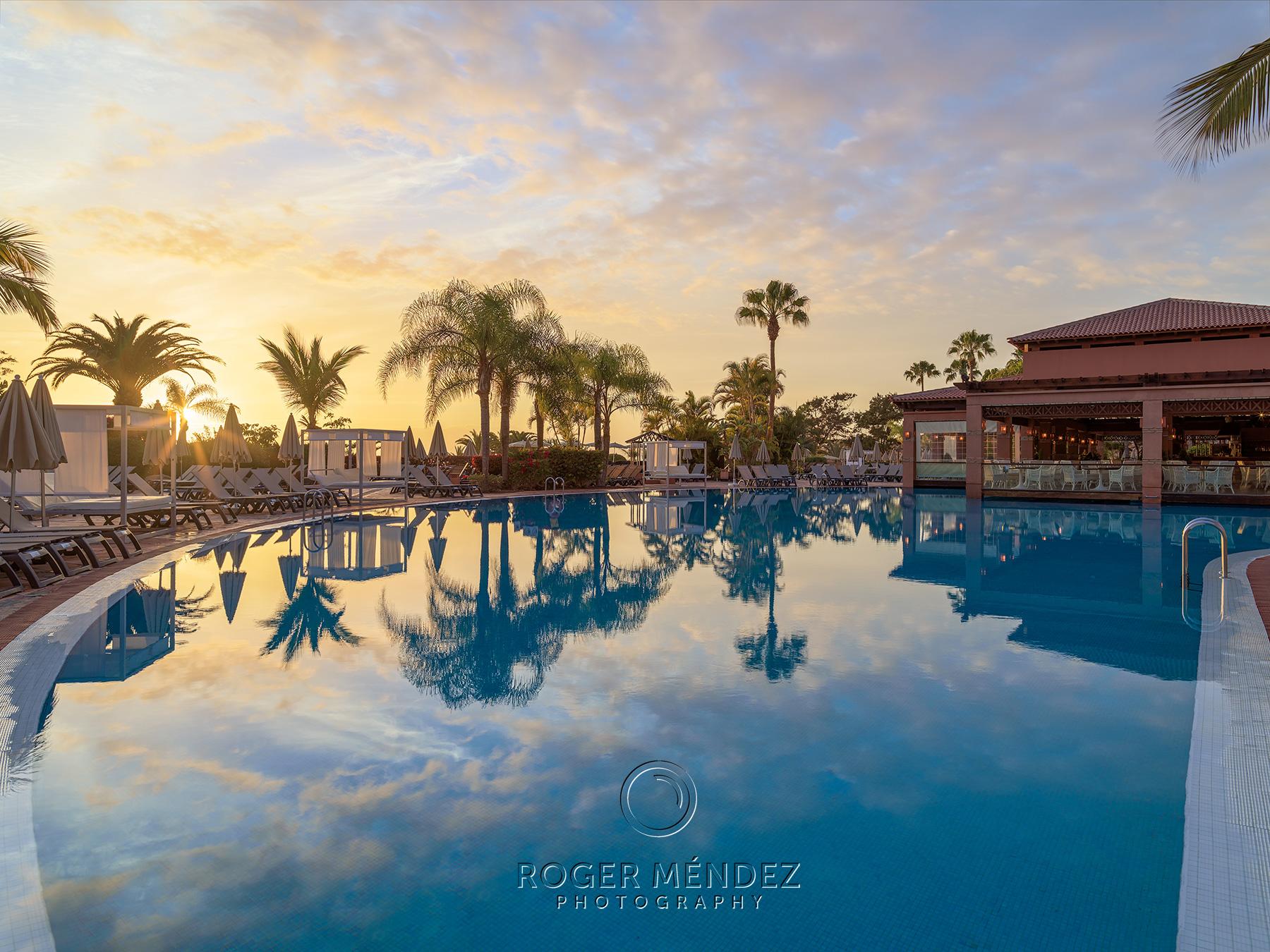 Fotografía de piscina principal al anochecer en el H10 Costa Adeje Palace